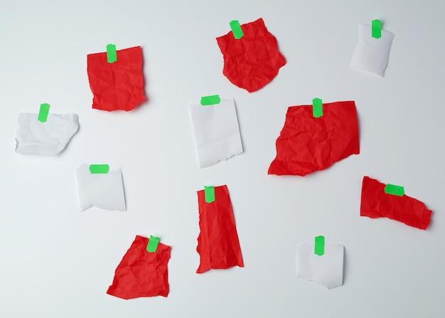 Много разорванных красных и белых кусочков бумаги, склеенных зеленой скотчем