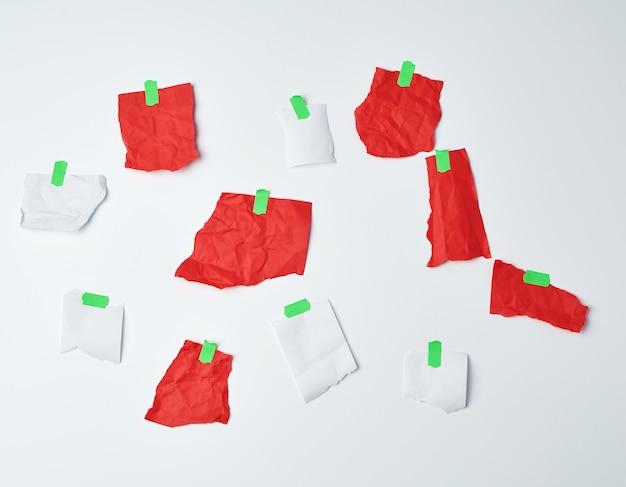 緑のスコッチテープで接着された破れた赤と白の紙片がたくさん
