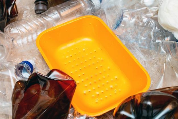 使用済みのプラスチック、くしゃくしゃにした空のボトル、パケット、プラスチック製のオレンジ色の皿がたくさん。汚染リサイクルエコ概念。