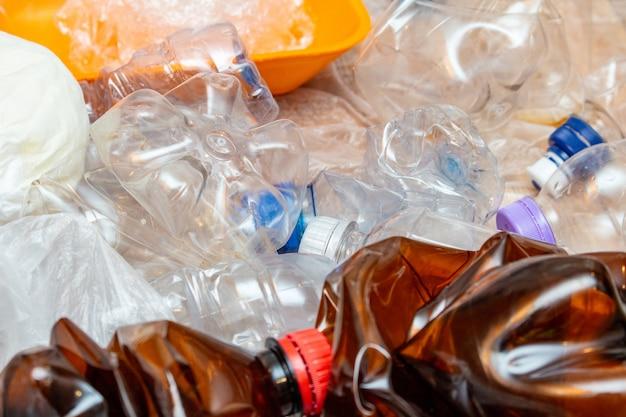 使用済みプラスチック、くしゃくしゃにした空のボトル、パケットがたくさん。プラスチック汚染リサイクルエコ概念。