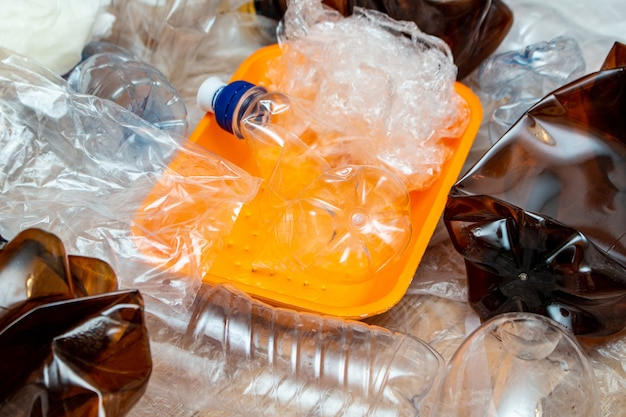 Много использованных пластиковых мятых пустых бутылок, пакеты, загрязнение, переработка, эко концепция фон