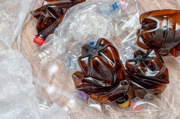 使用済みプラスチック、くしゃくしゃにした空のボトル、パケットがたくさん。汚染リサイクルエコ概念