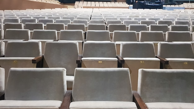A lot of old beige upholstered chairs without people in the hall for performances and films. background from many chairs in the stands in a concert hall or theater.