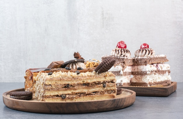 A lot of piece of cakes with cookies on wooden cutting board.
