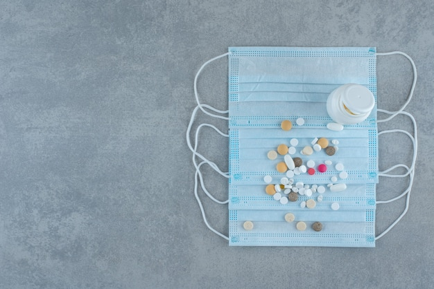 A lot of pills with medical mask on gray surface