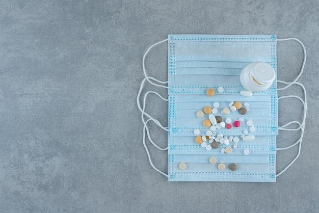 Molte pillole con mascherina medica sulla superficie grigia