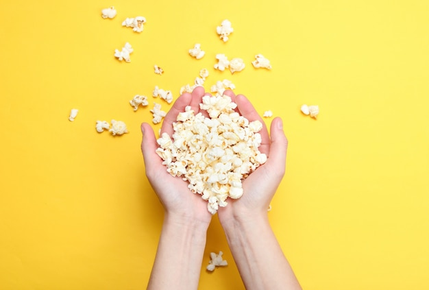 Lot of popcorn in  hands on yellow. top view,