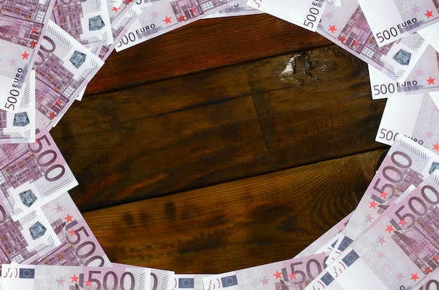 A lot of purple denominations worth 500 euros lie on a wooden surface