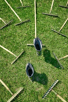A lot of rakes are lying on the lawn blocking the path, garden shoes make a choice of path