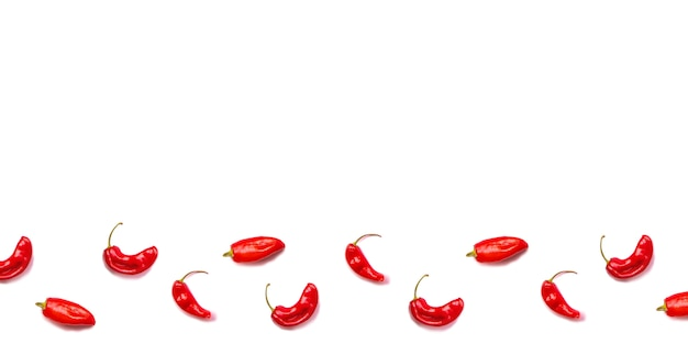 A lot of red hot chili peppers on a white background.