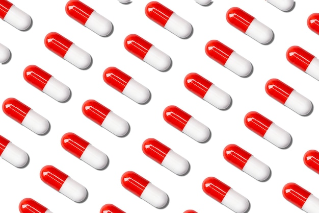 Lot of red and white medical capsules on a white background