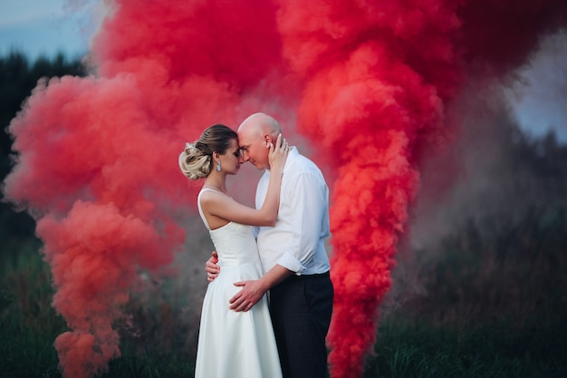 A lot of red and white smoke near beautiful woman in white dress and caucasian man in white shirt and black trousers