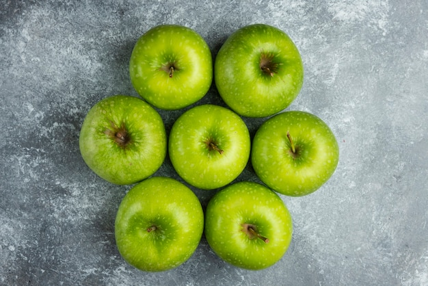 Molte mele mature sulla superficie di marmo.
