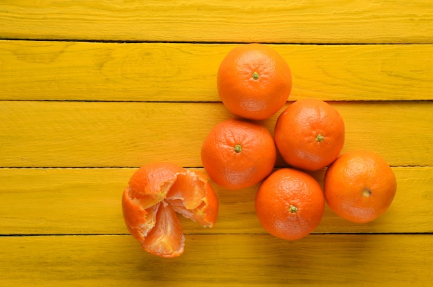 A lot of ripe mandarins on a yellow wooden table. top view. fruit concept.