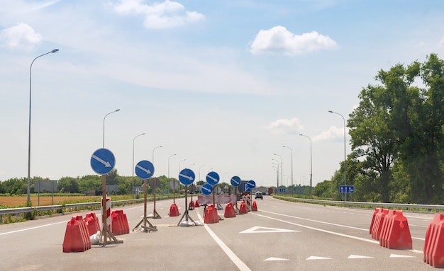 A lot of road signs showing directions on an asphalt highway.