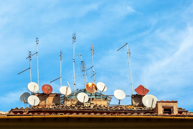 A lot of satellite dish antennas on the house against blue sky background in italy.