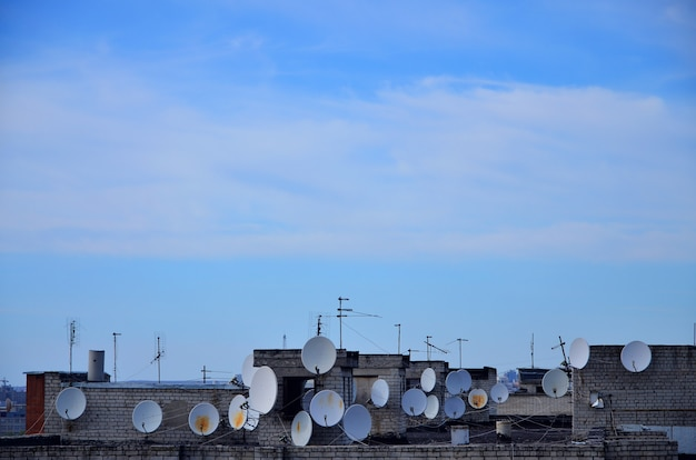 A lot of satellite television antennas on the rooftop under a blue sky