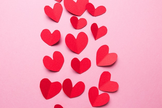 A lot of small hearts of red color against on a pink background. happy valentine's day.