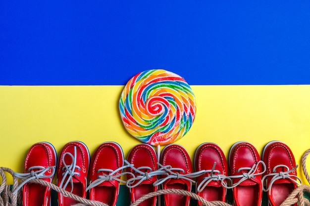A lot of small red boat shoes near big multi-colored lollipop