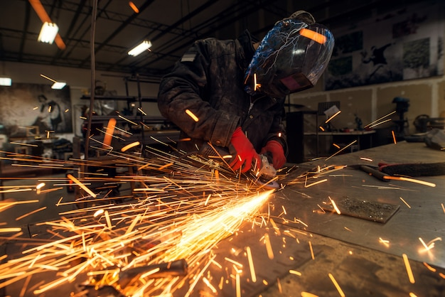 Lot of sparks and focused professional industrial worker with protection mask working with an electric grinder in a fabric workshop