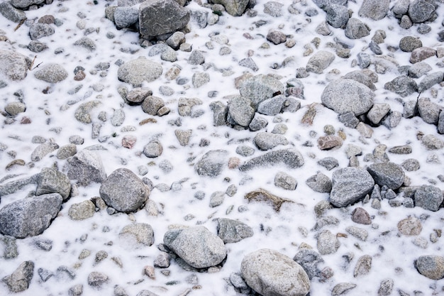 A lot of stones in the snow. difficult route in the mountains