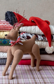 A lot of sweaters and pullovers different colours folded in two piles and deer toy.