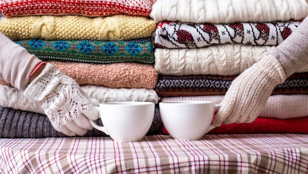A lot of sweaters and pullovers different colours folded in two piles and hands with two cups of coffee.