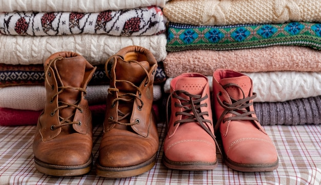 A lot of sweaters and pullovers different colours folded in two piles on the table with brown and red shoes