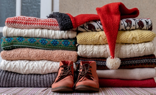A lot of sweaters and pullovers different colours folded in two piles on the table with old red shoes