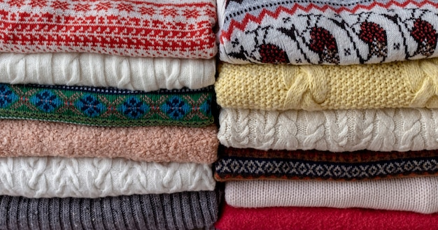 A lot of sweaters and pullovers different colours folded in two piles on the table.