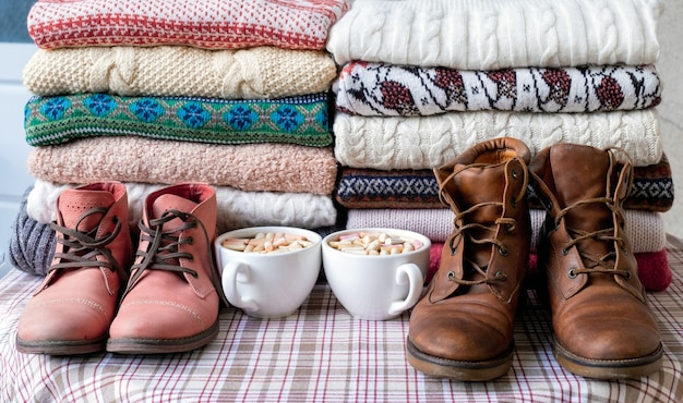 A lot of sweaters and pullovers different colours folded in two piles with brown and red shoes and cups of coffee.
