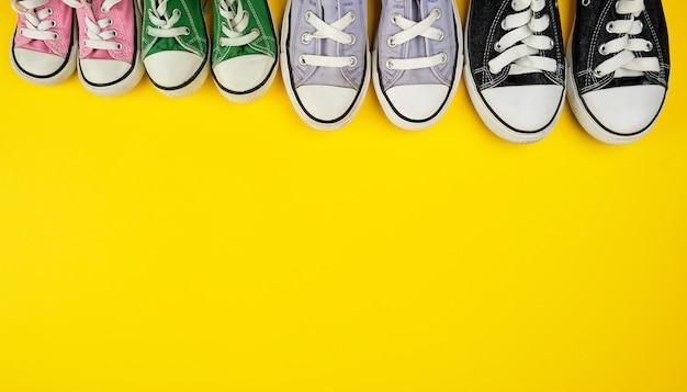 Lot of textile worn sneakers of different sizes on a yellow background