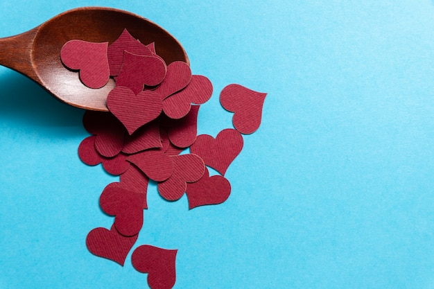 A lot of tiny burgundy hearts in a wooden spoon on a blue background.