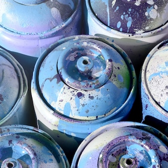 A lot of used blue metal tanks with paint for drawing graffiti