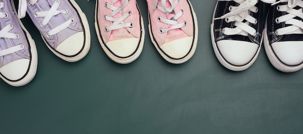 A lot of used textile sneakers on a green background, various sizes. family concept, friendship, top view, copy space