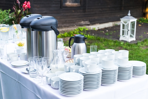 Lot of white porcelain coffee cups and large big thermos on the table in outdoors summer party