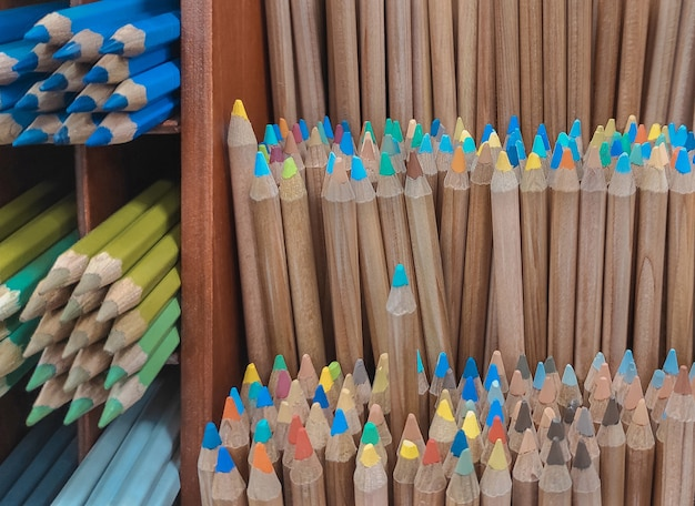 A lot of wooden colored pensils on shelf.