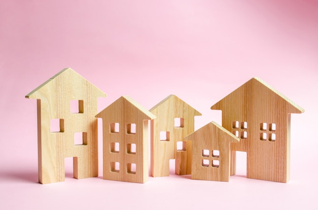 A lot of wooden houses on a pink background.