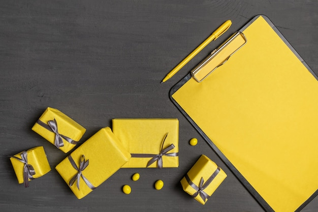 A lot of yellow gifts box and resume sheet on the gray colour