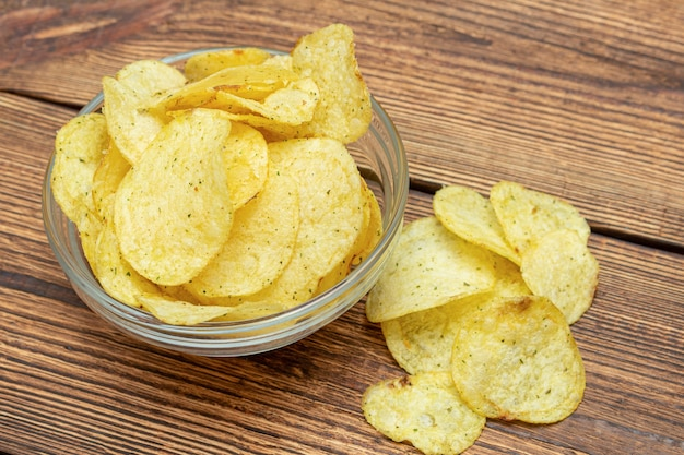 Lot of yellow potato chips in glass dish