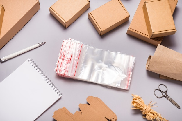Lot of zip lock bags and brown cardboard boxes on grey surface