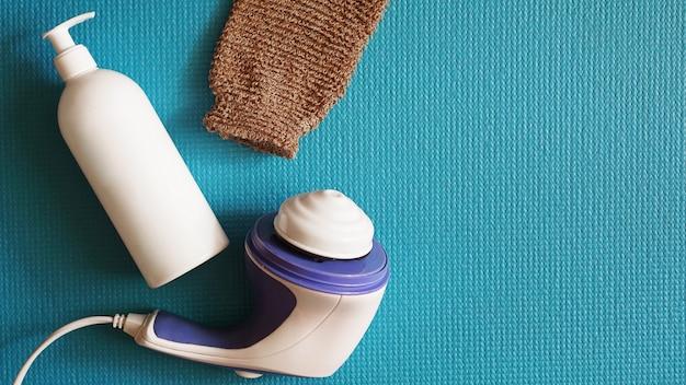 파란색 배경에 로션과 셀룰라이트 방지 마사지. 건강하고 아름다운 피부 개념.