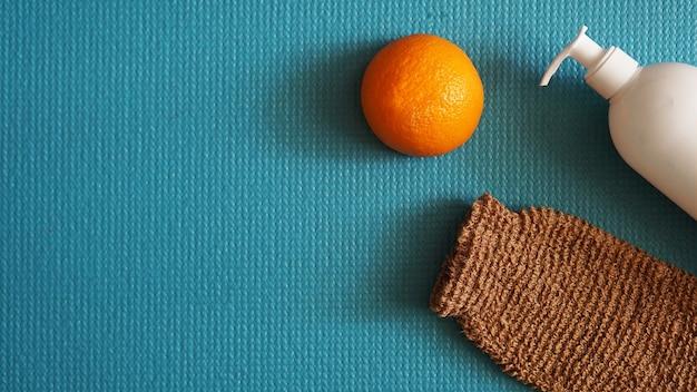 로션과 오렌지 과일 - 파란색 배경의 셀룰라이트 방지 개념