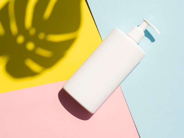 Lotion bottle mock-up next to monstera leaf shadow