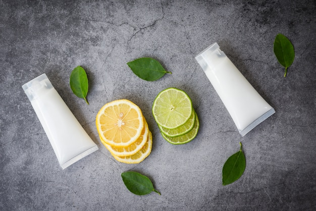 Бутылка лосьона, естественная для красоты лица и тела, а также органический минималистский образ жизни с ломтиком лимона и лайма и зелеными листьями травяных составов