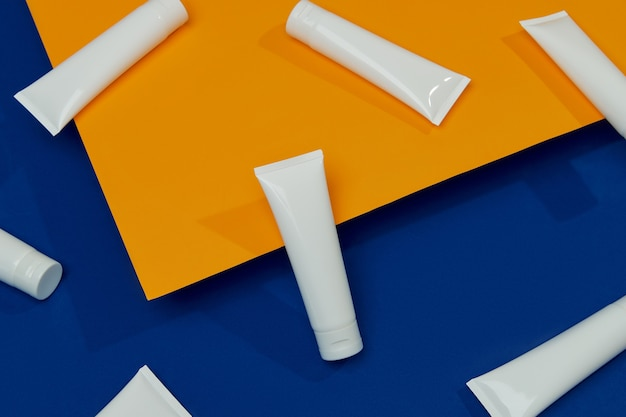 オレンジとブルーの背景にローションまたはクリームセットフェイスボディケア美容トリートメント