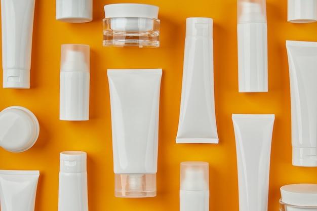 オレンジ色の背景ケア製品のスキンケアルーチンにローションまたはクリームをセット
