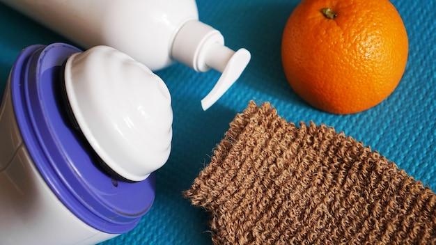 파란색 배경에 로션, 오렌지, 샤워 스폰지, 안티 셀룰라이트 마사지기. 건강하고 아름다운 피부 개념.