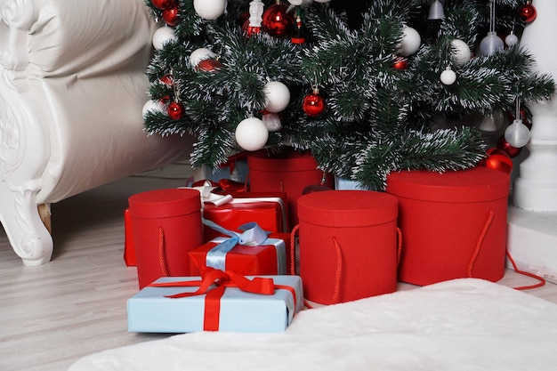 Lots of beautiful wrapped christmas presents in round boxes in red and blue under the christmas tree.