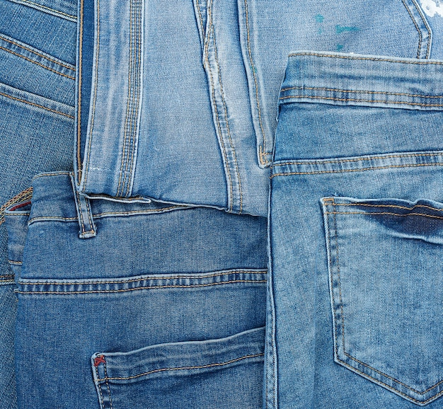 Lots of blue classic jeans stacked chaotically, back pocket
